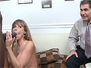 Darla Crane screws dark-hued knob before her hubby cleans up